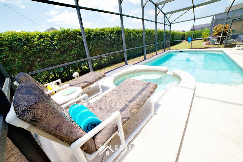 Two large lounge chairs overlooking jacuzzi spa and outdoor private pool at Sunshine Villa at Glenbrook Resort, a short-term vacation rental home in Orlando near Walt Disney World