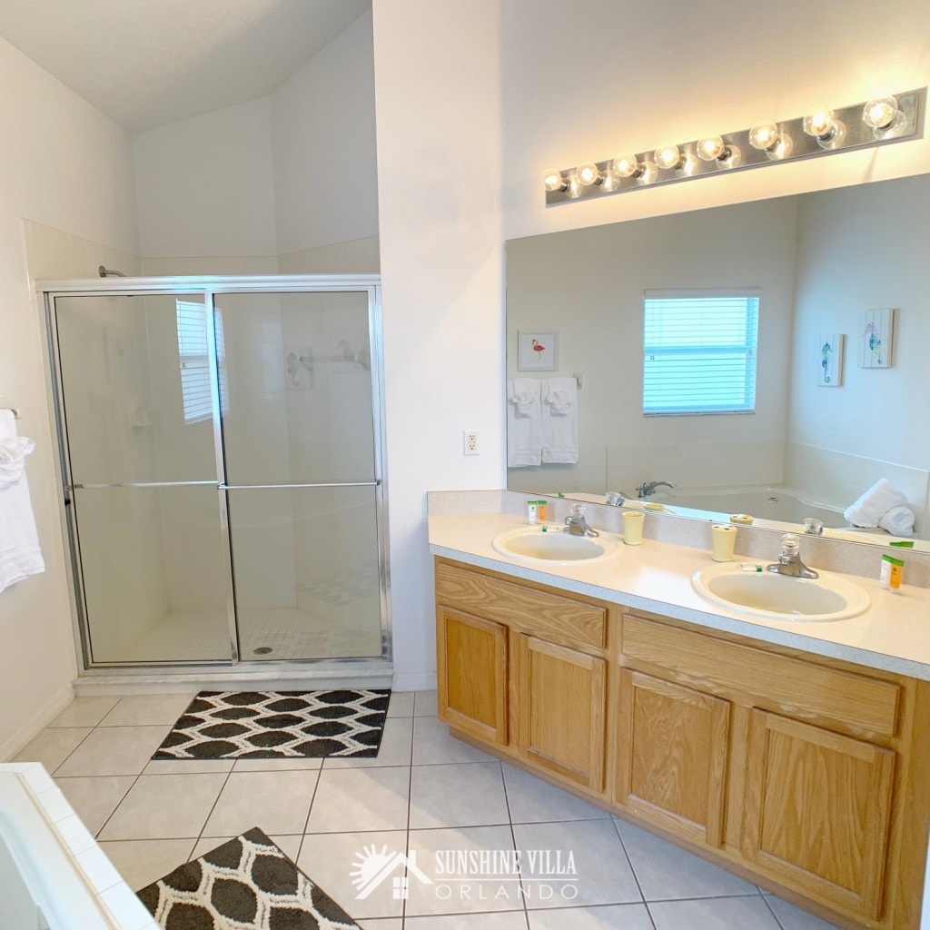 Large master bathroom with two sinks and a wide shower stall at Sunshine Villa at Glenbrook Resort, a short-term vacation rental home in Orlando near Walt Disney World