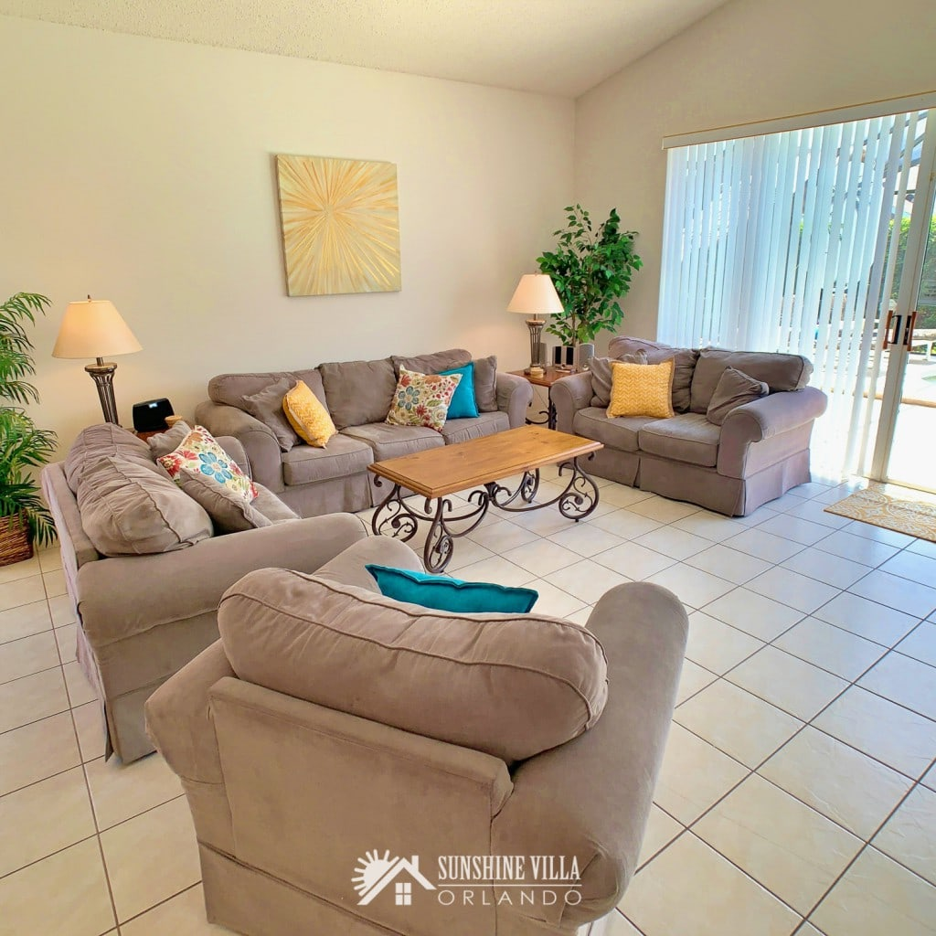Living Room with a couch, two love seats and a side chair at Sunshine Villa at Glenbrook Resort, a short-term vacation rental home in Orlando near Walt Disney World