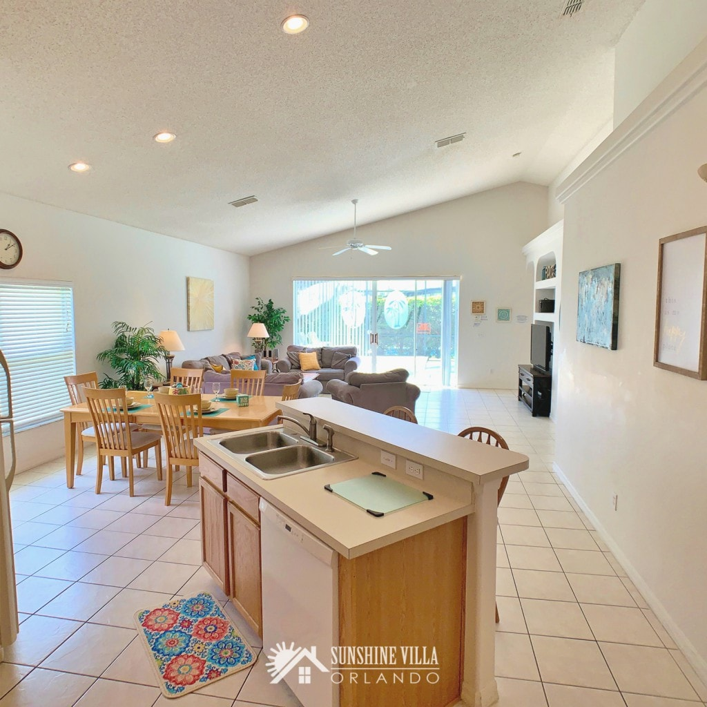 Kitchen Island with Dining Room and Living Room in the background at Sunshine Villa at Glenbrook Resort, a short-term vacation rental home in Orlando near Walt Disney World