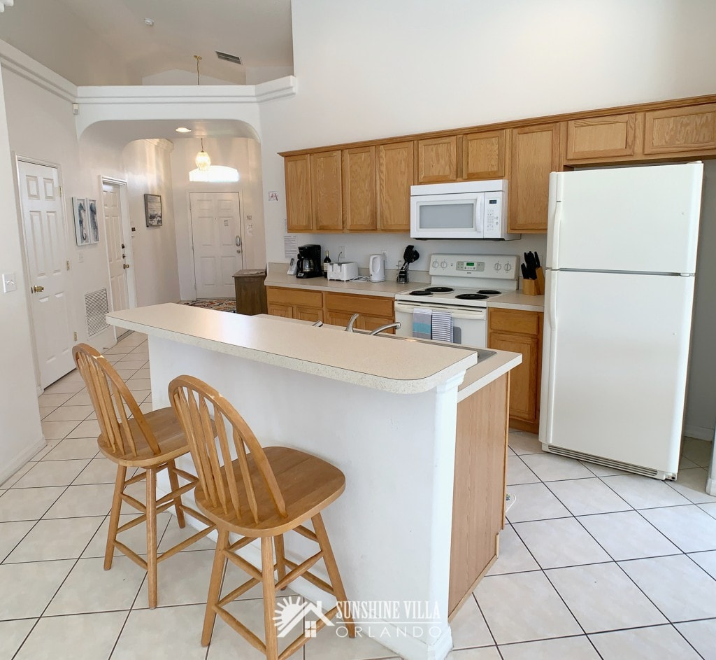 Kitchen island with two bar stools at Sunshine Villa at Glenbrook Resort, a short-term vacation rental home in Orlando near Walt Disney World