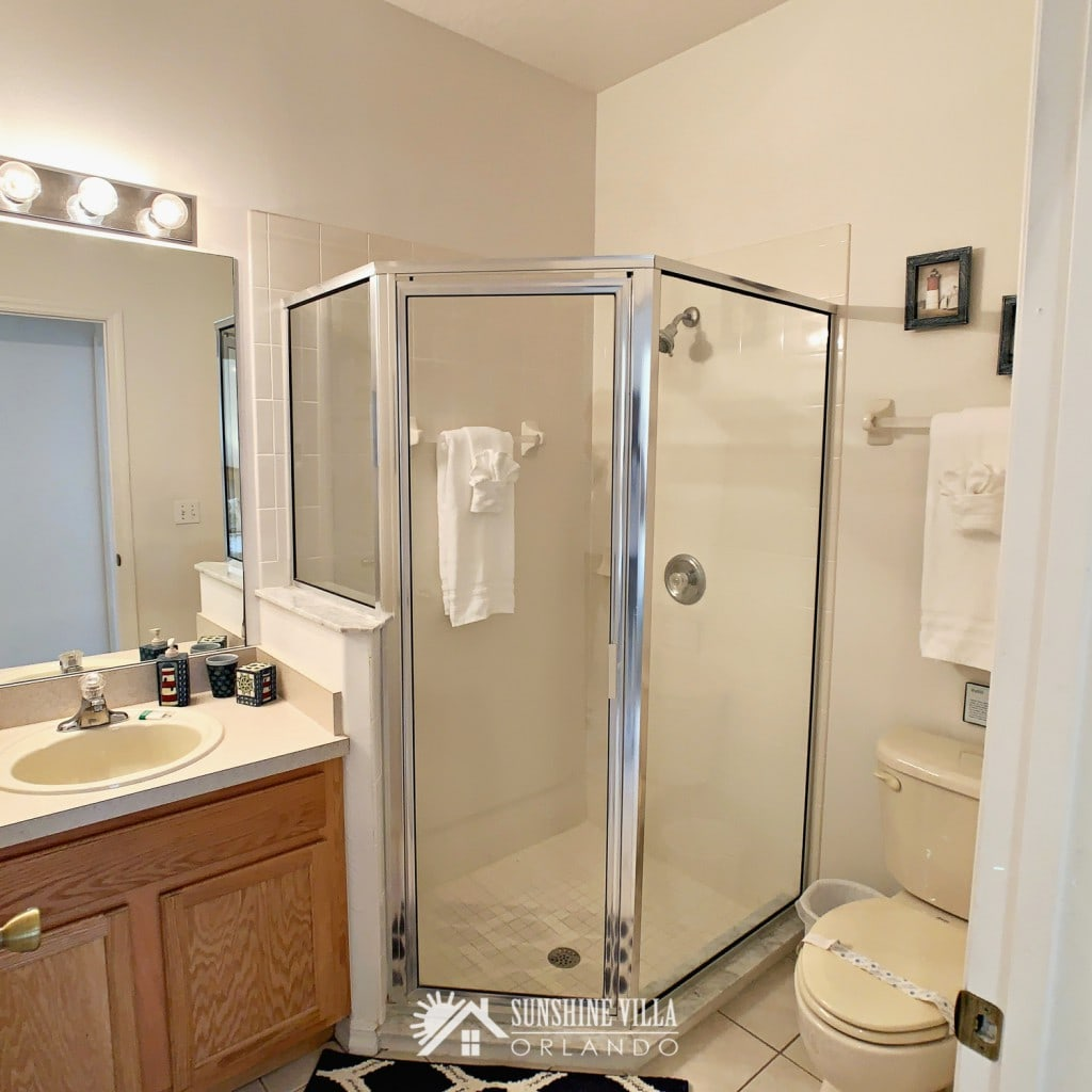 Bathroom near the two twin bedrooms at Sunshine Villa at Glenbrook Resort, a short-term vacation rental home in Orlando near Walt Disney World. A shower stall, vanity and a toilet.