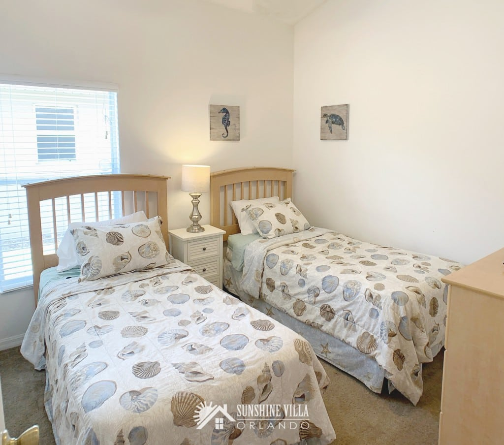 Bedroom with two twin beds at Sunshine Villa at Glenbrook Resort, a short-term vacation rental home in Orlando near Walt Disney World. Each twin bed has a sea shell print bedspread. There's also a small nightstand between the two beds and a seahorse and turtle art on the walls.